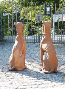 Zwei Hundeskulpturen vor einem Tor